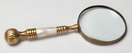 A 20th Century antique style magnifying glass having a brass and mother of pearl handle. 26cm long.