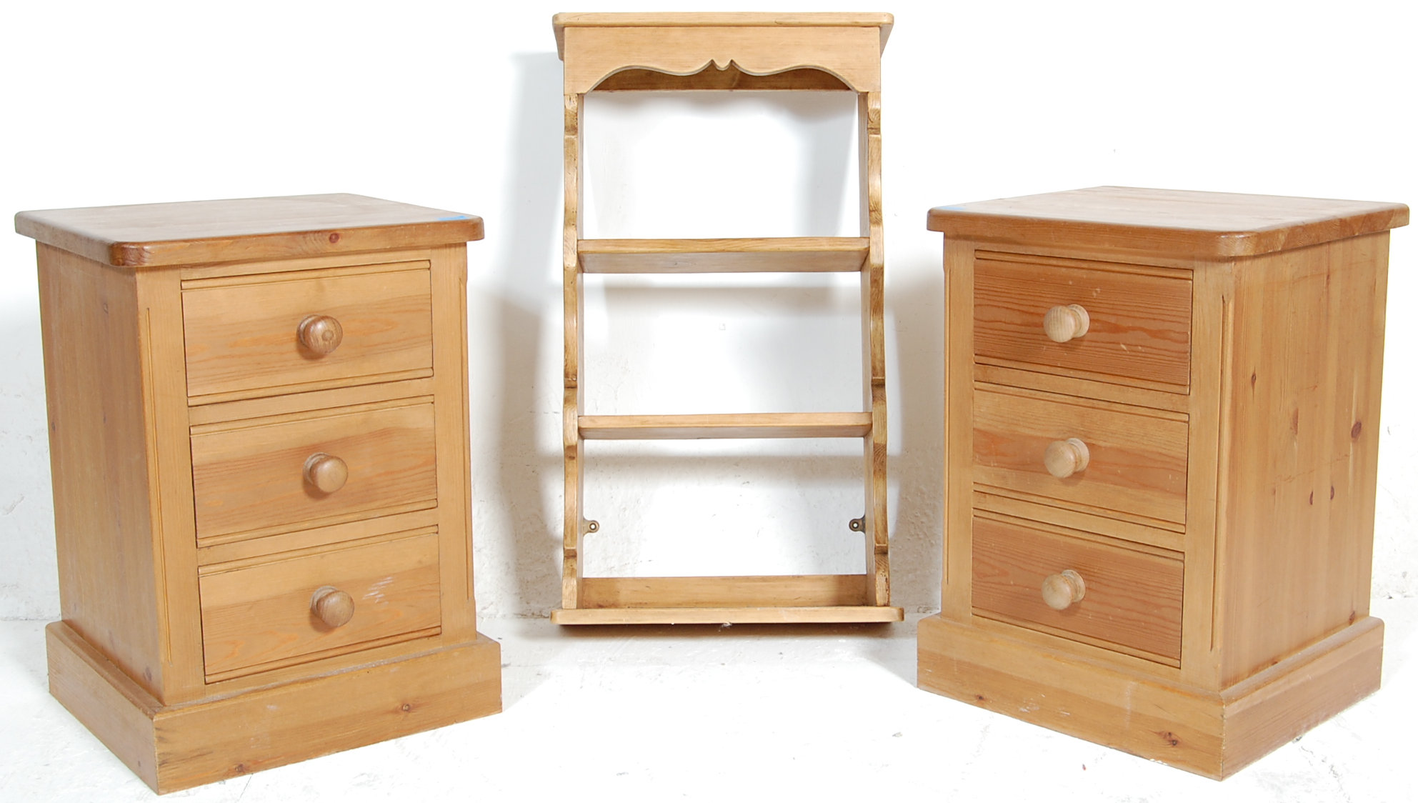 A pair of vintage pine bedside pedestal chests having a shaped edge over...
