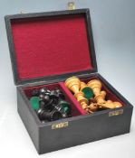 A 20th Century carved chess set having boxwood and ebonised weighted pieces complete with a