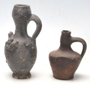 Two antique 16th Century style stoneware hand modelled jugs to to include an oil jug with applied