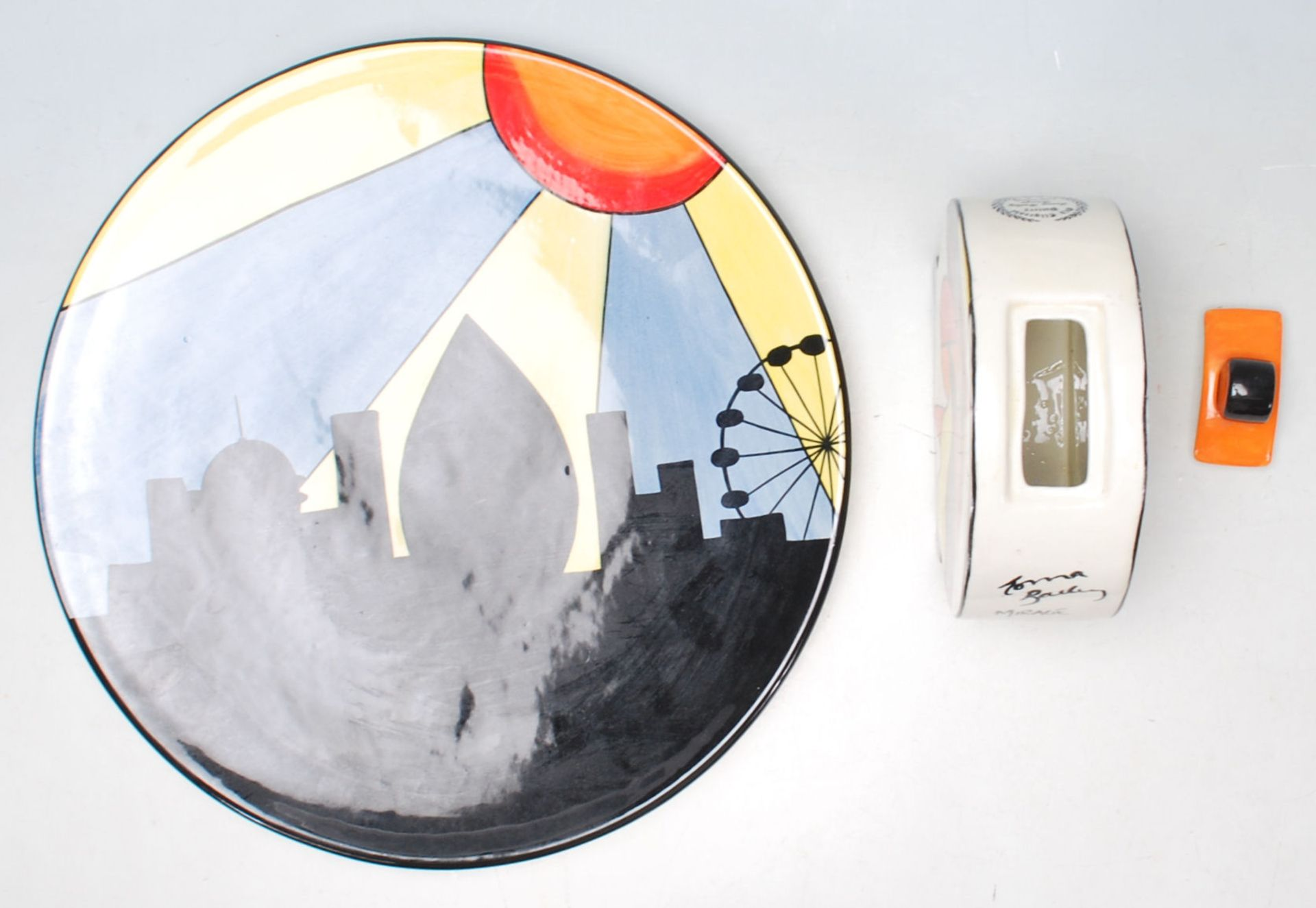 Los 7 - Lorna Bailey ceramic charger plate being hand painted with black, blue, yellow and orange colours,