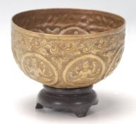 An antique Middle Eastern brass prayer bowl with hand-carved religious figurine to the centre,