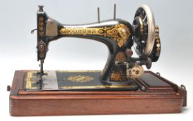 A vintage early 20th Century oak cased Singer Sewing machine having a good art deco sarcophagus