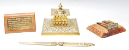A good collection of brass desk tidy items to include a brass inkwell, brass letter opening, brass