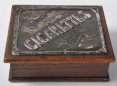 An Arts and Crafts early 20th Century wooden cigarette box / case having a hinged lid with a