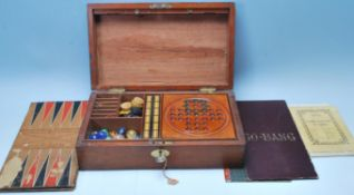 An early 20th Century wooden games compendium box being fully appointed with retro games to