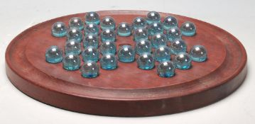 An early 20th Century Edwardian mahogany solitaire board of round form having 32 green glass marbles