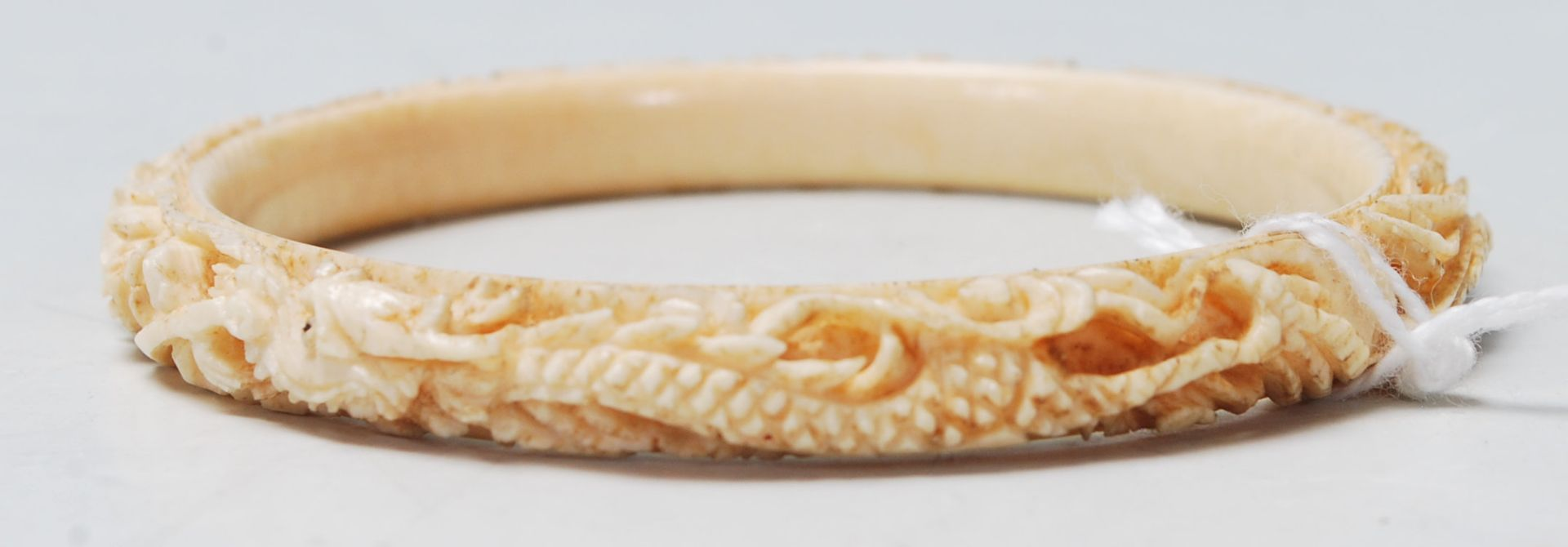 Los 298 - A 19th Century Chinese carved ivory bangle of typical circular form featuring stone inset eyes and a