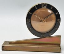 A 1920's Art Deco 8 days mantel clock having a round case with black enamelled case with arabic