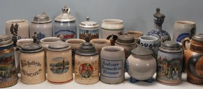 A large collection of German blue and grey stoneware jugs and beer steins, some having pewter