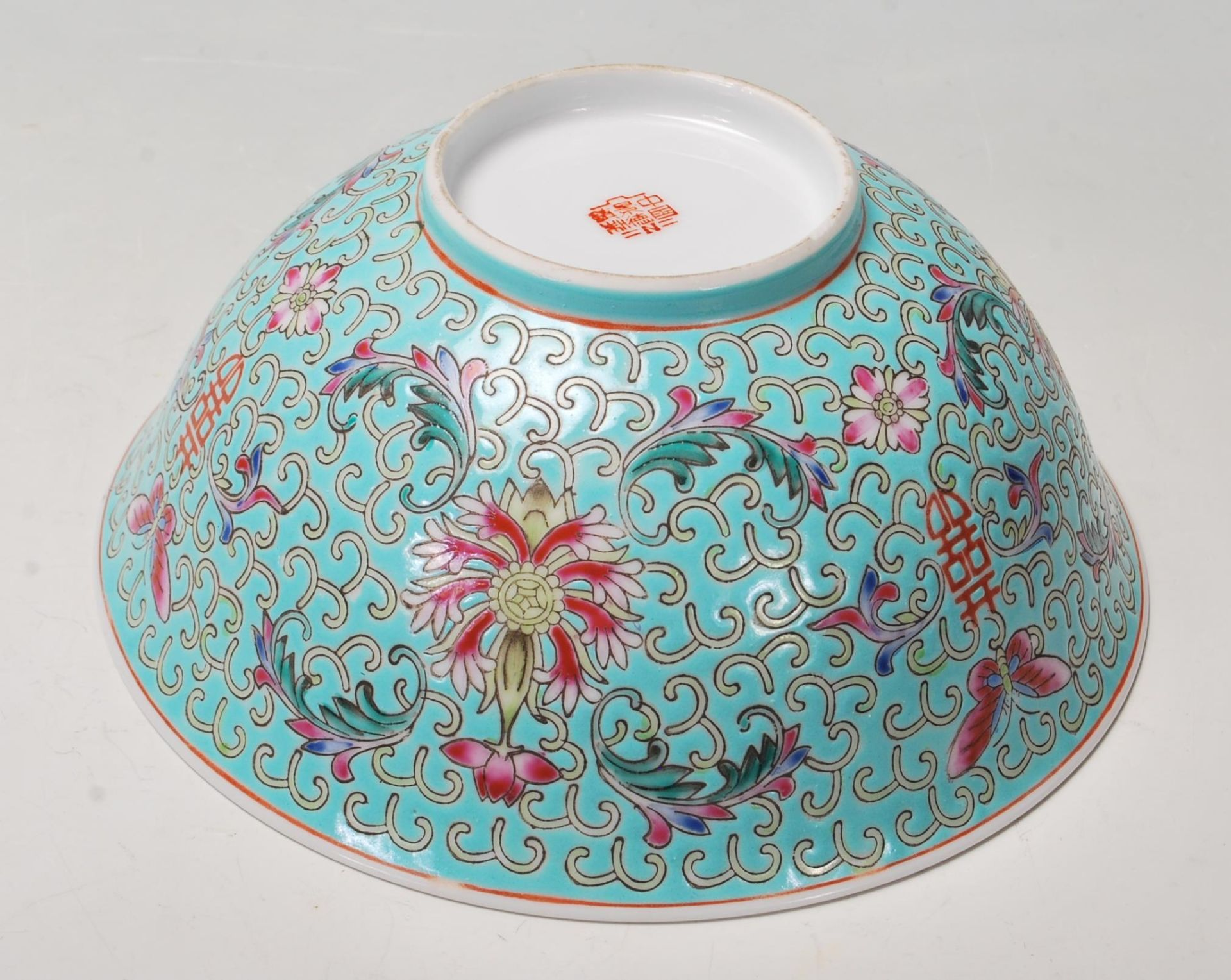 Los 76 - A vintage 20th Century Chinese bowl decorated with floral, butterfly and Shou emblem designs on a