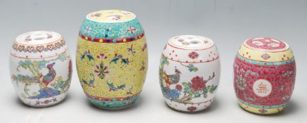 A group of four 20th Century Chinese storage jars of barrel form to include a red enamelled jar with