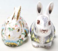A pair of Royal Crown Derby paperweights both in the shape of rabbits including Springtime Bunny &