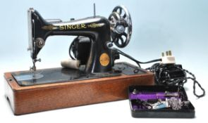 A vintage mid 20th Century Singer electric tabletop sewing machine having black body with gold