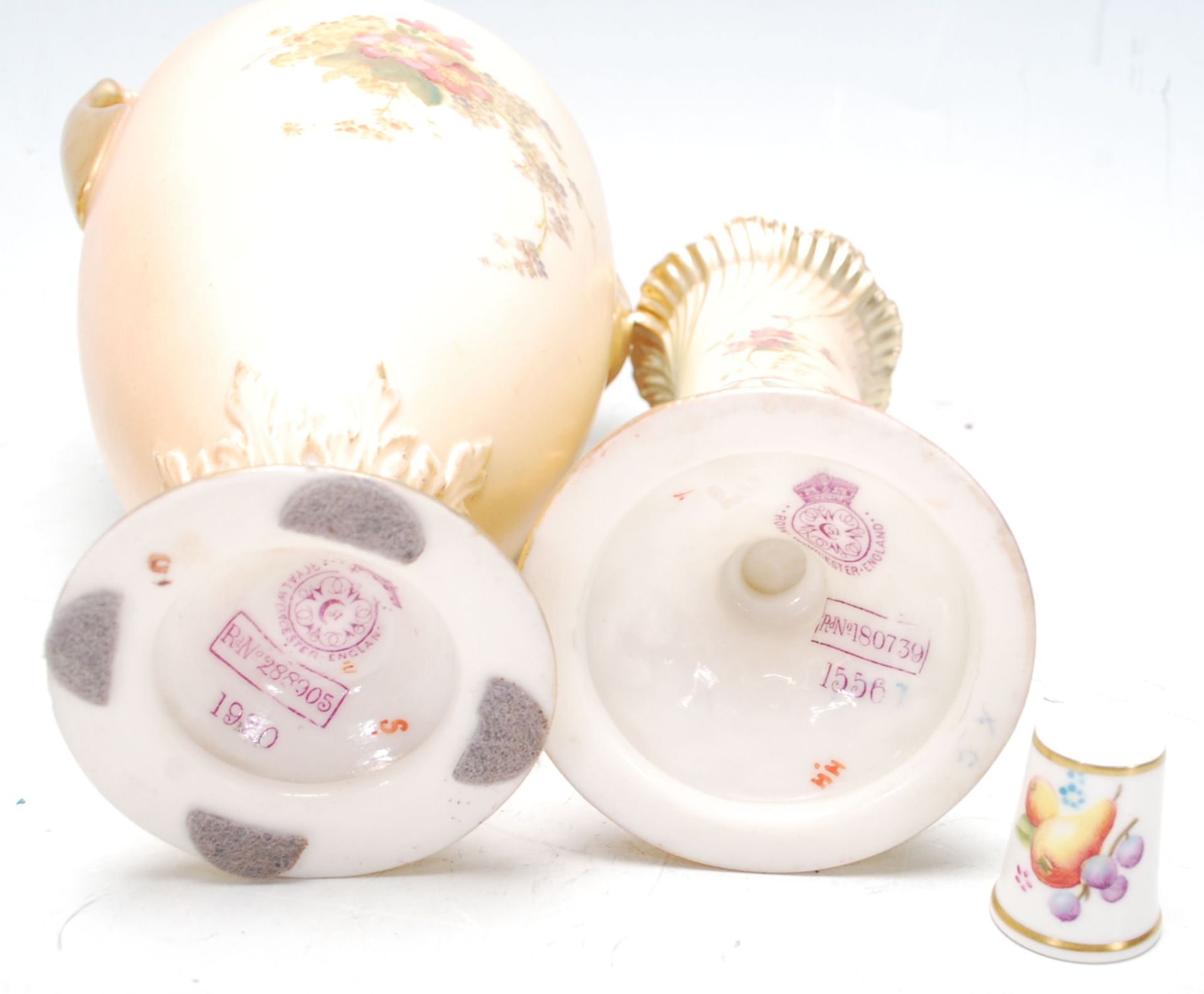 Los 19 - Group of Three Royal Worcester blush ivory vases, hand painted with flowers and gilded decoration,