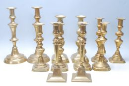 An early 20th / late 19th Century set of six tabletop brass candlesticks being raised on a squared