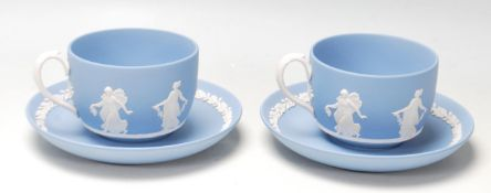 A pair of antique early 20th century Wedgwood dancing hours Jasperware tea cups and saucers with