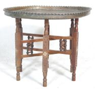 An early 20th Century antique tray opium table raised on six fruit wood legs united by stretchers