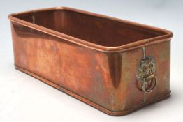 A vintage copper planter trough of rectangular form having a lipped edge and a lions head handle