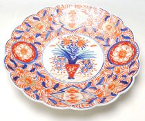 A 19th Century Japanese Imari charger plate with scalloped rim, typical decoration with a vase of
