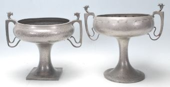 A pair of early 20th Century pewter twin handled vases raised on columnal supports with footed bases