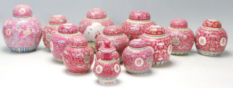 A collection of thirteen 20th Century Chinese famille rose ginger jars being decorated with red