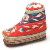 A 20th Century Chinese folk art pin cushion in the form of a shoe having embroidered floral