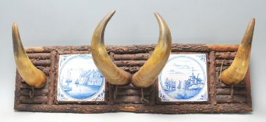 Early 20th century tribal inspired coat rack having four bovine horns flanked by two blue and