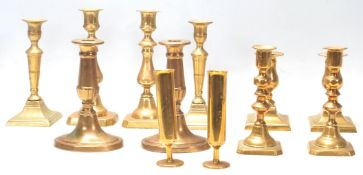 A good collection of mid 20th Century brass candlesticks raised on squared, circular and oval