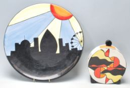 Lorna Bailey ceramic charger plate being hand painted with black, blue, yellow and orange colours,