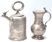 An 18th Century German pewter vessel / tankard having bulbous form with scroll handle sitting on