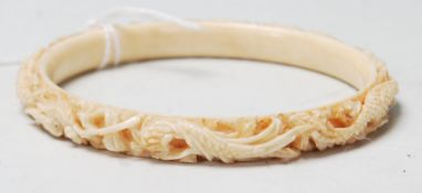 A 19th Century Chinese carved ivory bangle of typical circular form featuring stone inset eyes and a