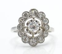 An 18ct white gold and diamond cluster ring. The r