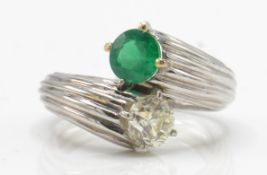 An emerald and diamond toi et moi ring. Estimated