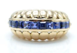 14ct gold and sapphire dome ring. The ring set with square cut panel of sapphires