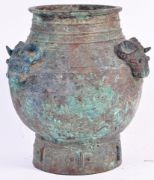 RARE BELIEVED SHANG DYNASTY CHINESE ARCHAIC BRONZE VESSEL  A rare and exceptional believed Shang or Zhou Dynasty Chinese antique bronze archaic ritual sacrificial vessel circa 1100BC. The pot of globular form with banded rim and the body set with scrolled horned beasts raised on circular foot. The body having verdigris patina with lightly engraved detailing throughout. Measures: 22cm tall. | East Bristol Auctions