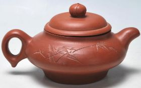 A 20th Century Chinese Yi Xing red clay teapot raised on a footed base with engraved bamboo design