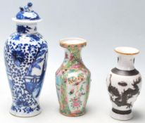 A group of three Chinese porcelain vases to include a blue and white hand painted lidded vase having