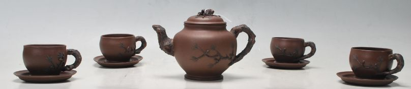 A 20th century Chinese yi xing terracotta teapot, cups and saucers having a handle and spout in