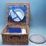 A VINTAGE RETRO WICKER PICNIC BASKET COMPLETE WITH PLATES, KNIVES, FORKS AND THERMOS.