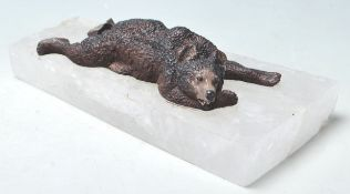 A PAPER WEIGHT COMPRISED OF A CAST IRON BEAR LAYIN