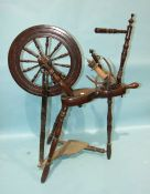 An early-19th century turned mahogany spinning wheel, (incomplete), 94cm high.