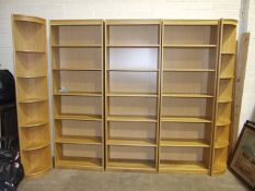 A large modern run of oak-effect shelving/bookcase shelves, with corner end sections, 287cm wide,