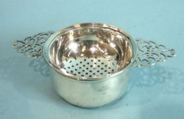 An Elkington & Co. tea strainer on stand, the strainer with two pierced handles, on plain circular