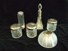A collection of silver-mounted cut-glass dressing table bottles and a silver-mounted glass match