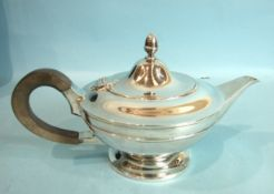 A plain circular teapot of compressed form, the hinged lid with acorn finial, by Goldsmiths,