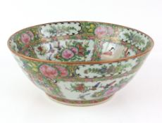 A Canton famille rose bowl, decorated with typical panels of Manchu/Chinese figures and Natural