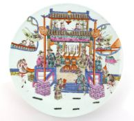 A famille rose dish of circular form decorated with a narrative scene of figures seated for