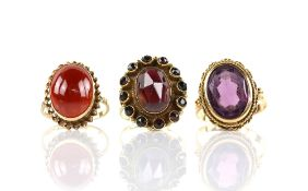 Three paste set rings, one purple paste set stone ring, mount testing as 18 ct, size P, a red