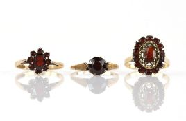 Three garnet set rings, one single stone with ornately decorated shoulders, size P and two cluster